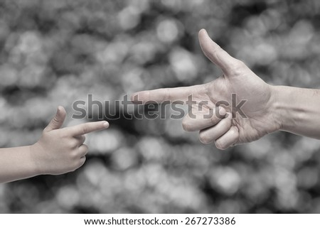 Caucasian male and boy desaturated hands pointing, or gun gesture, on blurred black and white background. - stock photo