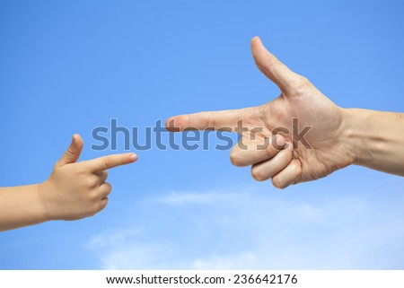 caucasian male and boy hand pointing, or gun gesture, on blue sky with some clouds background - stock photo