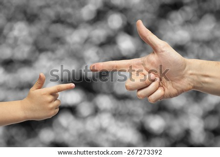 Caucasian male and boy pointing, or gun gesture, on blurred black and white background.  - stock photo