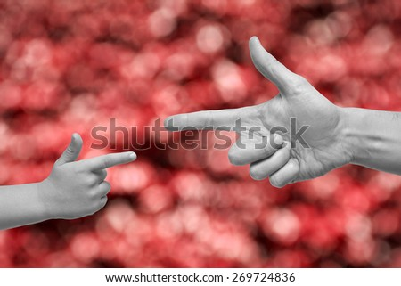 Caucasian male and boy with desaturated hands pointing, or gun gesture, on blurred red background. - stock photo