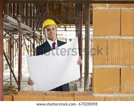 caucasian male architect holding blueprints and looking at camera. Horizontal shape, waist up, front view, copy space - stock photo