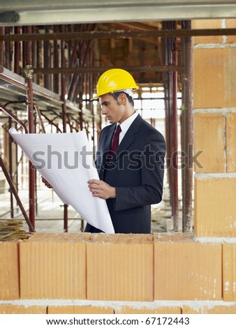 caucasian male architect holding blueprints near brick wall. Vertical shape, waist up, side view, copy space