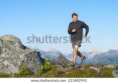 Caucasian male athlete in shorts and shirt runs across rocky summit with beautiful snow covered mountains in background - stock photo