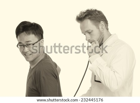 Caucasian male doctor examining asian male patient with stethoscope. Isolated on white. - stock photo