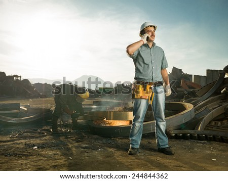 caucasian male engineer standing in recycling center, talking on phone, with man welding metal in background - stock photo