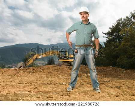 caucasian male engineer standing on construction site holding hammer, with excavator in background