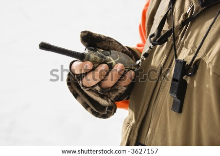 Caucasian male hand holding walkie talkie.