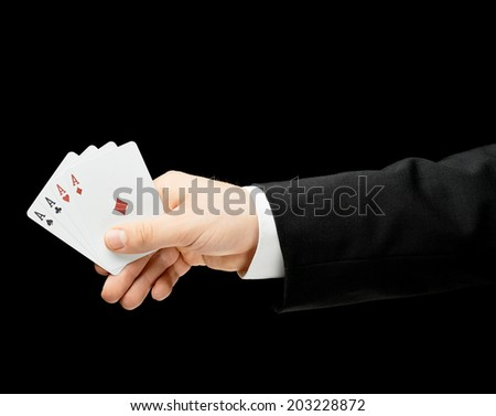 Caucasian male hand in a business suit holding four aces in a palm, low-key lighting composition, isolated over the black background - stock photo