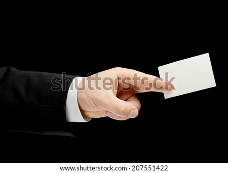 Caucasian male hand in a business suit, holding the white empty business card, low-key lighting composition, isolated over the black background - stock photo