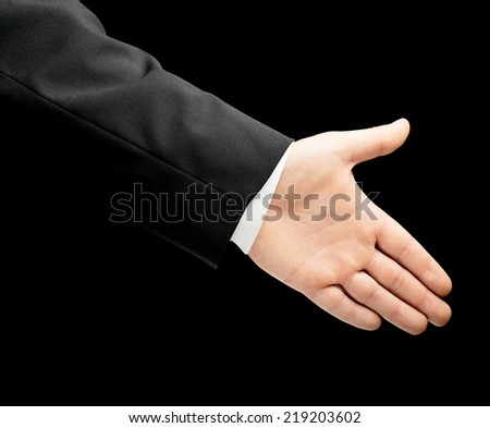 Caucasian male hand in a business suit, offering a handshake with an opened palm, low-key lighting composition, isolated over the black background - stock photo