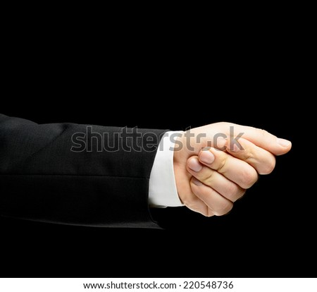 Caucasian male hand in a business suit, palm clenched in a fist, showing the direction with the thumb finger, low-key lighting composition, isolated over the black background - stock photo