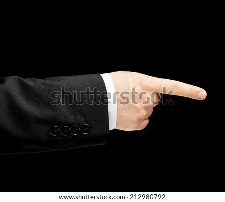 Caucasian male hand in a business suit, pointing to something with an index finger, low-key lighting composition, isolated over the black background - stock photo