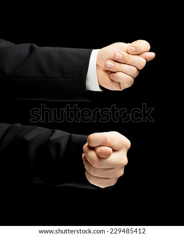 Caucasian male hand in a business suit, showing the offensive fig gesture sign, low-key lighting composition, isolated over the black background, set of two images - stock photo