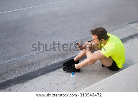 Caucasian male jogger in headphones using smart phone for choose the music of play-list and continue his fit training,young sports man resting after diary morning jog outdoors,copy space area for text - stock photo