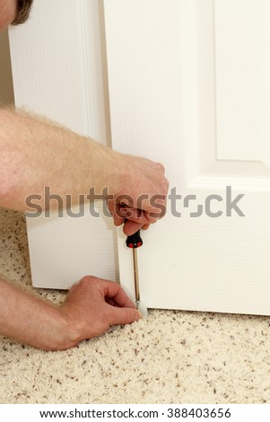 Caucasian male using a screwdriver to screw in a bypass door guide at the bottom middle carpeted floor of a home closet door. Installing a white plastic door guide.