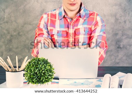 Caucasian male with crossed arms sitting at office desk with plant and other items looking at a laptop screen - stock photo