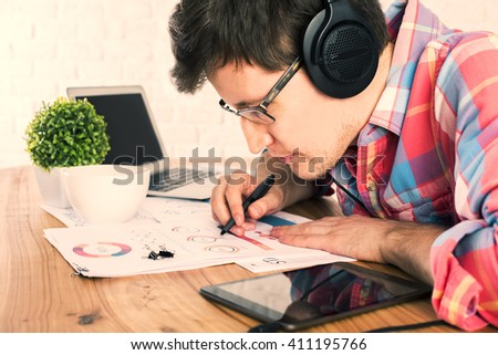 Caucasian male with headphones analyzing business report placed on wooden desk with tablet, laptop, coffee mug and other items - stock photo