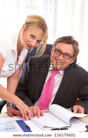 Caucasian man and woman looking at camera in office.  - stock photo