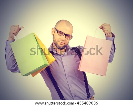 Caucasian man bald, with a beard, glasses with colorful shopping paper bags isolated  - stock photo