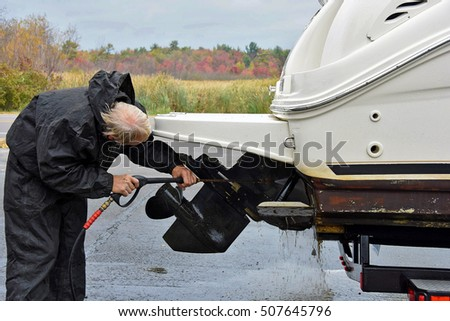 Caucasian man cleaning boat prop with pressure washer