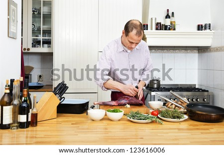 Caucasian man cutting meat on chopping board at kitchen counter - stock photo