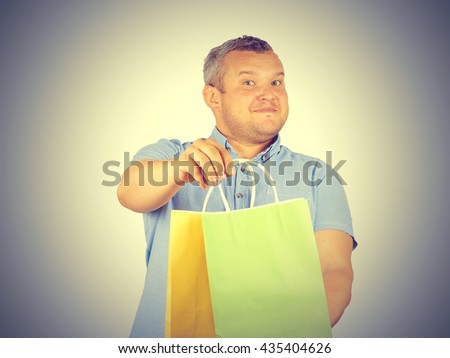 Caucasian man fat,  with colorful shopping paper bags isolated on background.    - stock photo