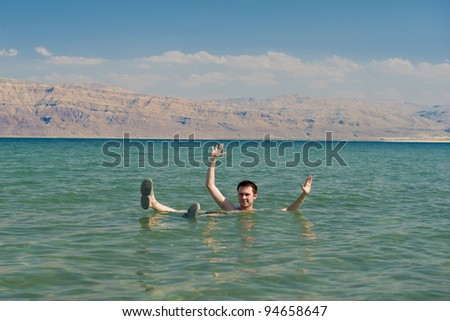 Caucasian man floating in the waters of the Dead Sea in Israel - stock photo