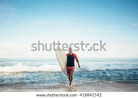Caucasian man goes out from the blue ocean with his white longboard surf and smile