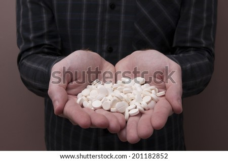 Caucasian Man Holding a Bunch of Pills and Capsules / Capsules and Pills / Medicine - stock photo