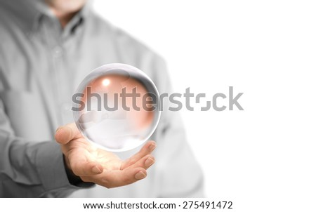 Caucasian man holding a glass or crystal ball, copy space on the left side of the image. Magician or fortuneteller background concept over white. - stock photo