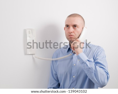 Caucasian man holding an intercom on a white wall. - stock photo