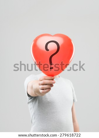 caucasian man holding heart shaped ballon with question mark in front of his head, against grey background - stock photo