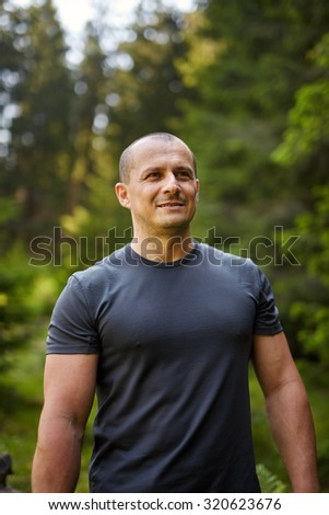 Caucasian man in a pine forest, closeup portrait with selective focus