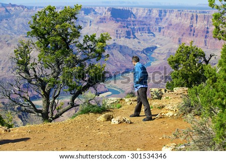 Caucasian man in mid forties cautiously looking over cliff at Grand Canyon, Arizona - stock photo