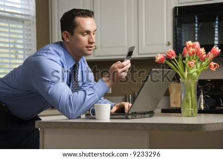 Caucasian man in suit using laptop computer and cellphone in kitchen. - stock photo