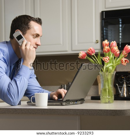 Caucasian man in suit using laptop computer and talking on cellphone in kitchen. - stock photo