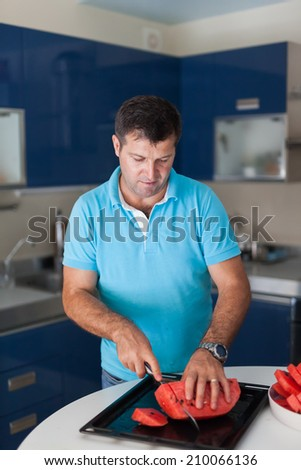 Caucasian man in the kitchen preparing portions of sliced watermelon - stock photo