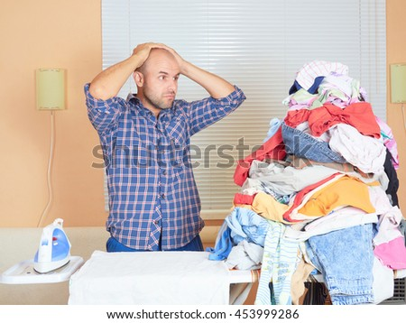 Caucasian man ironed clothes in the room near the window. Homework. - stock photo