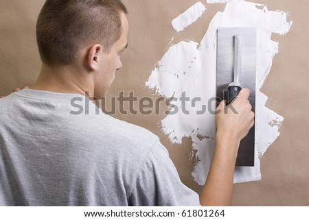 Caucasian man laying plaster on a brown wall. - stock photo