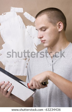 Caucasian man plastering a brown wall with white plaster. - stock photo