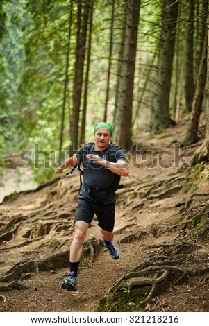 Caucasian man running in the pine forest forest, outdoor fitness concept - stock photo