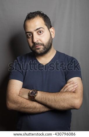 Caucasian man standing inside studio with grey background - stock photo