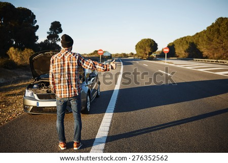 Caucasian man trying stop cars in travel because his car broken down. Young man stand on freeway and shows thumbs up. Young interracial man in their twenties.  - stock photo