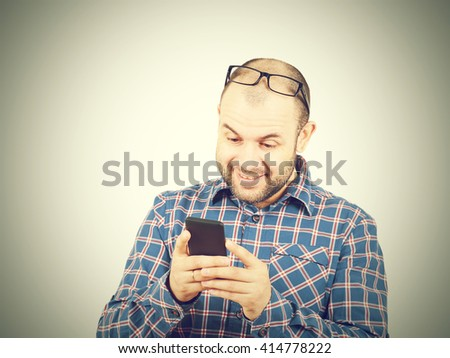 Caucasian man typing a message on mobile phone. Isolated on gray background.