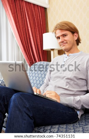 Caucasian man using laptop in the living room alone