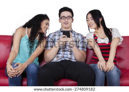 Caucasian man using mobile phone to send message near the curious friends - stock photo
