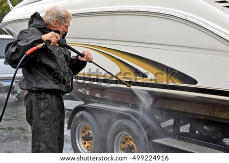 Caucasian man using pressure washer to clean power boat hull