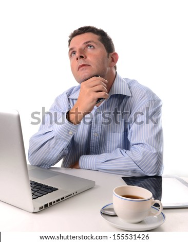caucasian man wearing a blue business shirt  thinking and worried about his future with his smart phone in his hand at a desk on a white background. - stock photo