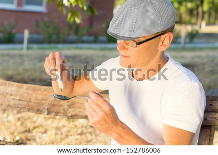 Caucasian man wearing a white T-shirt and a cap filling a syringe with injectable heroin - stock photo