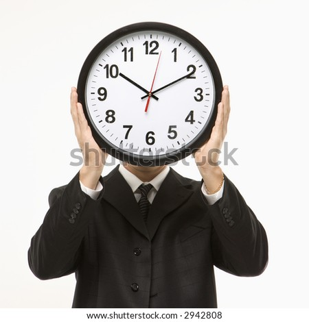 Caucasian man wearing suit holding clock in front of face.